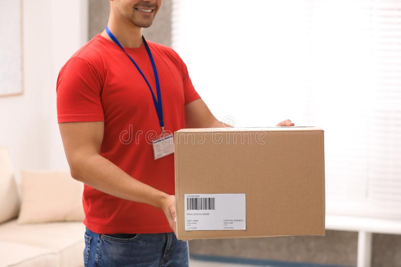 Young courier holding parcel indoors. Delivery service. Young courier holding parcel indoors, closeup. Delivery service stock photography