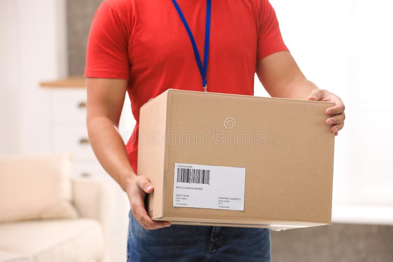 Young courier holding parcel indoors. Delivery service. Young courier holding parcel indoors, closeup. Delivery service stock image