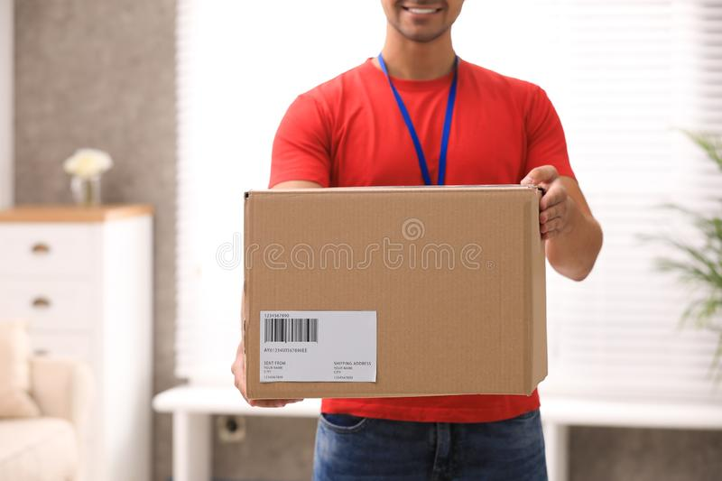 Young courier holding parcel indoors. Delivery service. Young courier holding parcel indoors, closeup. Delivery service royalty free stock image