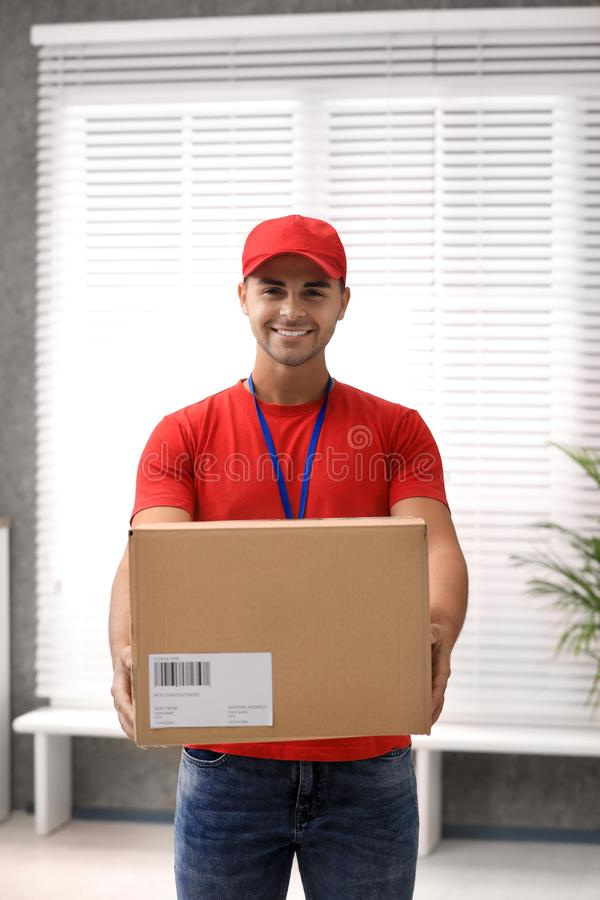 Young courier holding parcel. Delivery service. Young courier holding parcel indoors. Delivery service royalty free stock photo