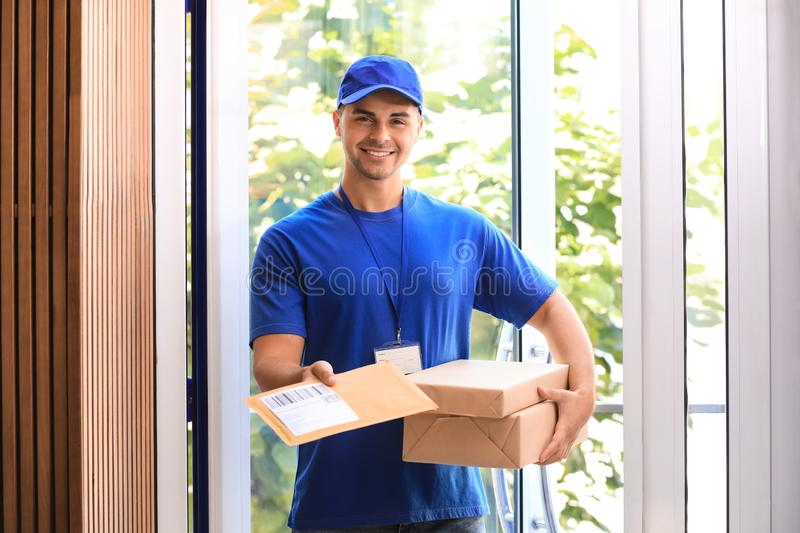 Young courier holding parcels on doorstep. Delivery. Service stock images