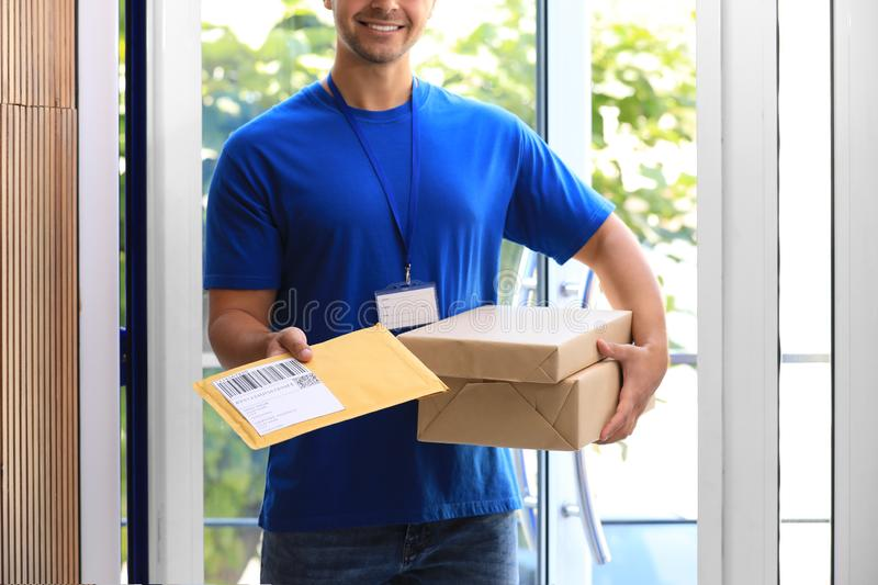 Young courier holding parcels on doorstep. Delivery service. Young courier holding parcels on doorstep, closeup. Delivery service royalty free stock photo