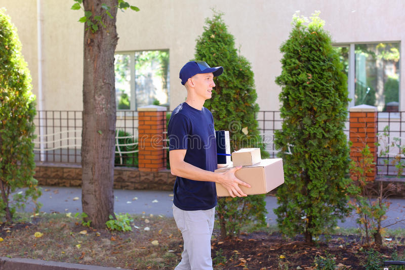 Young Courier Man Carring Order in Hands, Smiling at Camera and royalty free stock photos