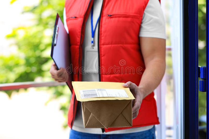 Young courier with parcels and clipboard on doorstep. Delivery service. Young courier with parcels and clipboard on doorstep, closeup. Delivery service royalty free stock images