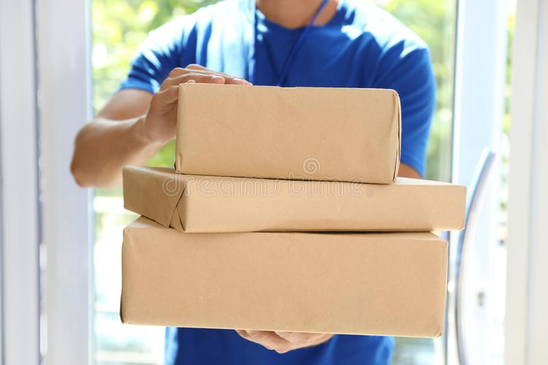 Young courier with pile of parcels indoors. Closeup stock image