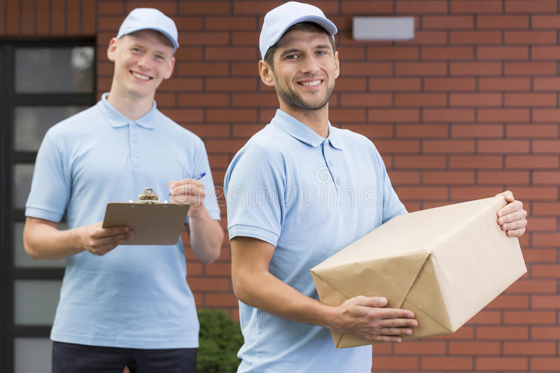 Young couriers with package and clipboard stock photos