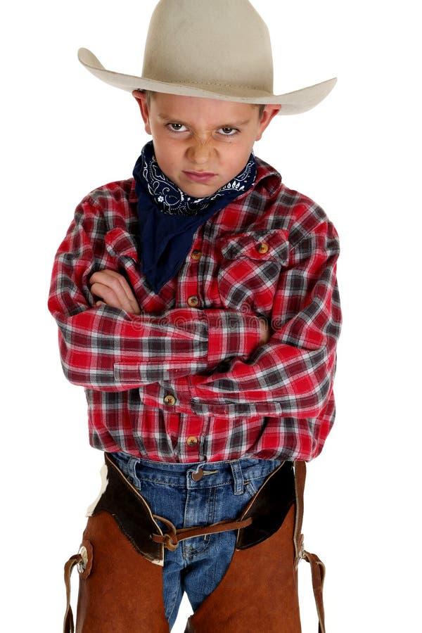 Young cowboy glaring at camera wearing hat and cha. Young cowboy glaring at camera hat chaps royalty free stock photos
