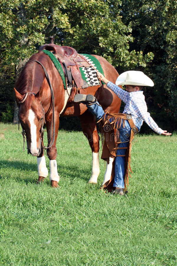 Young Cowboy Mounting Horse Royalty Free Stock Photography