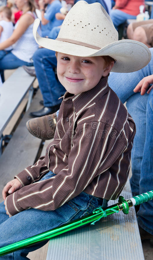 Young Cowboy with a Ninja Sword. A young cowboy sitting on bleachers watching a rodeo with a plastic ninja sword tied to his jeans stock photos