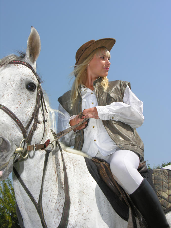 Young cowgirl. Young attractive woman riding in the summer day royalty free stock images