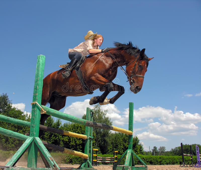 Young cowgirl jumping with chestnut horse. In summer day stock photo
