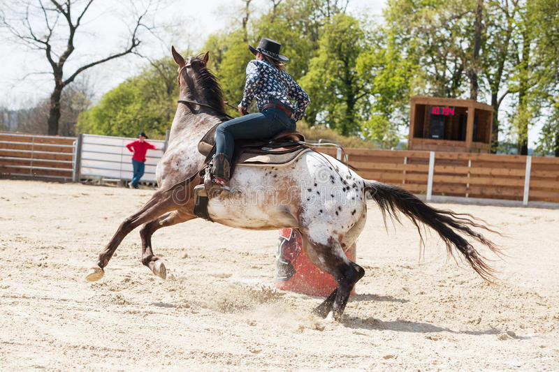 Young cowgirl riding a beautiful paint horse in a barrel racing event at a rodeo. Young cowgirl riding a beautiful paint horse in a barrel racing event at a stock photo