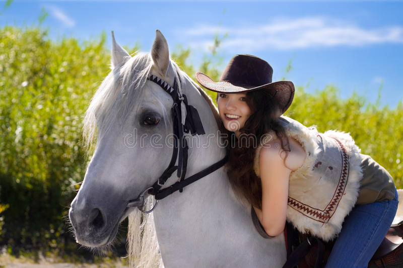 Young cowgirl on white horse smile. Blue sky royalty free stock photos