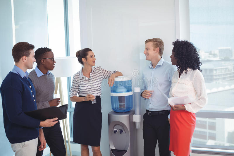 Young coworkers discussing at office. Young coworkers discussing while standing at office stock photos