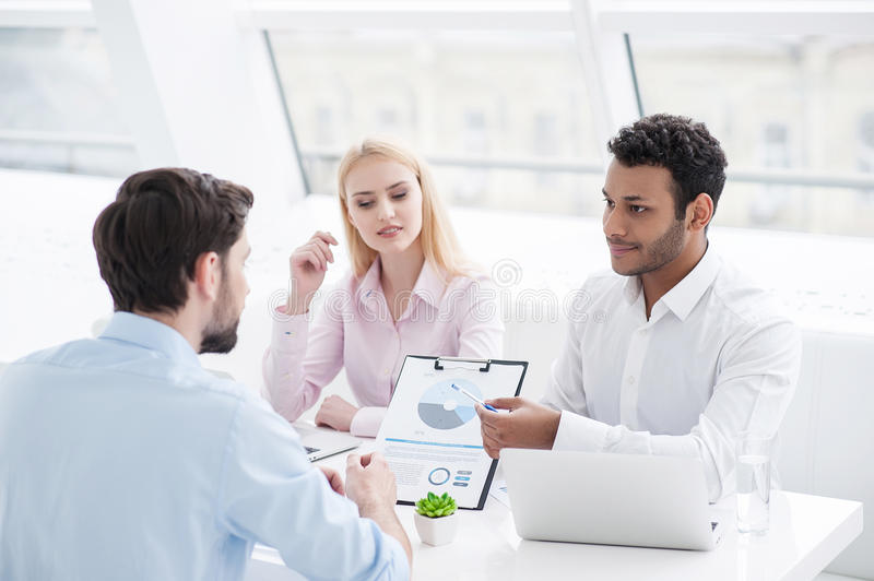 Young coworkers having brainstorming session in modern office stock photography