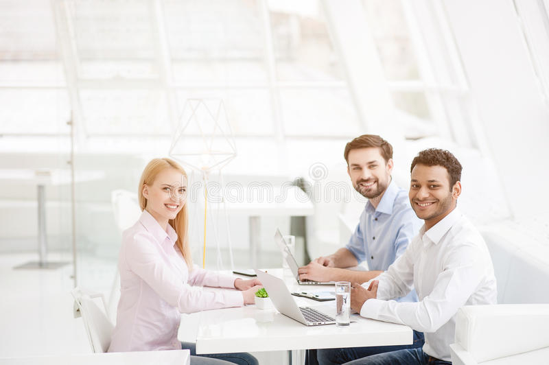 Young coworkers having brainstorming session in modern office royalty free stock photos
