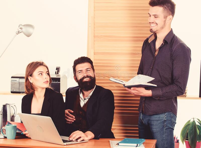Young coworkers. People making great business discussion in modern coworking office. Business people working and stock photo