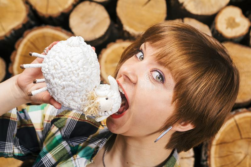 Young and crazy-hungry european short-haired girl wants to eat lamb meat. Food and restaurant concept. Close-up portrait on wooden stock image