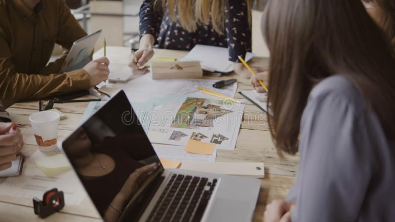 Young creative business team in modern office. Multiethnic group of people working on architectural design together. royalty free stock image