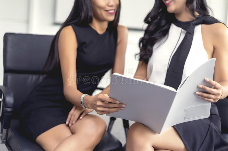 Young creative coworker team sitting and talking, working and discussing new planning project, holding document file in office, royalty free stock images