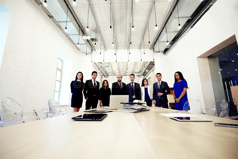 Young creative multi ethnic group of architects posing while standing near table with open laptop computer and paper documents stock photo