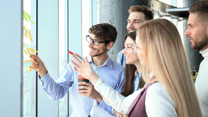 Young creative startup business people on meeting at modern office making plans projects with post stickers on glass. royalty free stock image