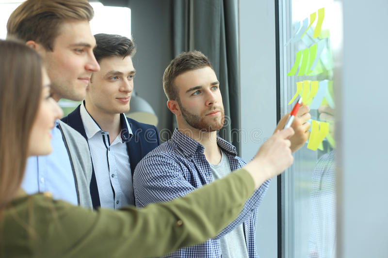 Young creative startup people on meeting at modern office making plans and projects with post stickers on glass. stock image