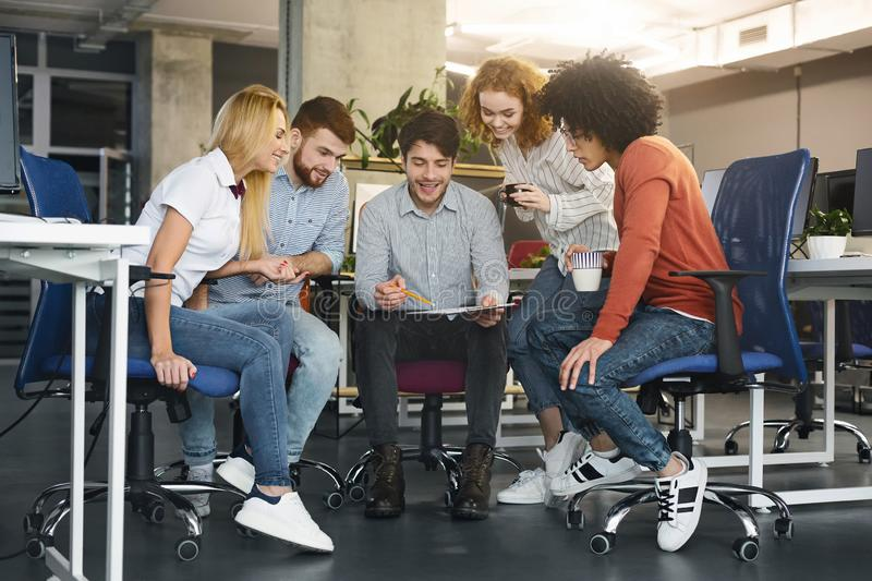 Young creative team discussing new project in coworking space stock photography