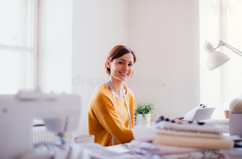 Young creative woman in a studio, startup of small tailoring business. Young creative woman with laptop working in a studio, startup of small tailoring business stock photography