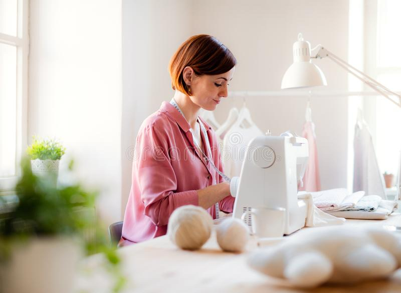 Young creative woman in a studio, working. A startup of tailoring business. Young creative woman in a studio, working on sewing machine. A startup of small royalty free stock photography