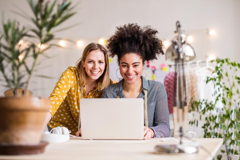 Young creative women with laptop in studio, startup business. Portrait of young creative women with laptop working in a studio, startup business royalty free stock photo