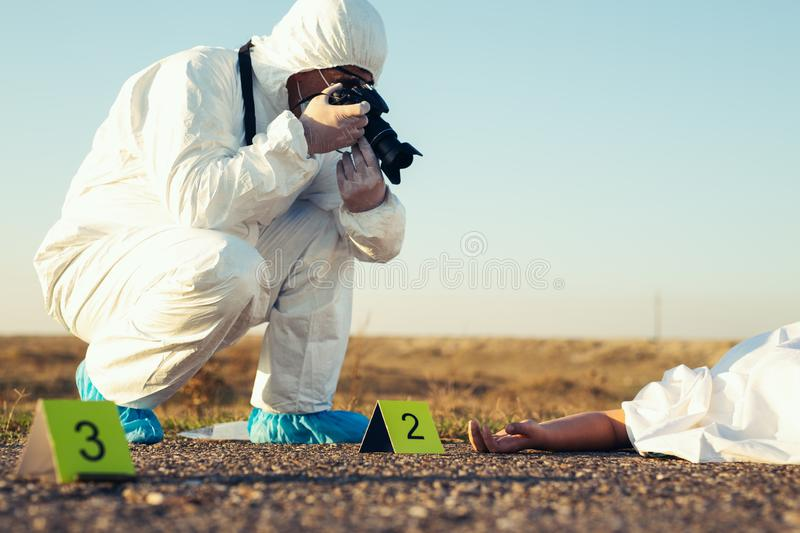 Criminological expert collecting evidence at the crime scene. Young Criminological expert collecting evidence at the crime scene royalty free stock image