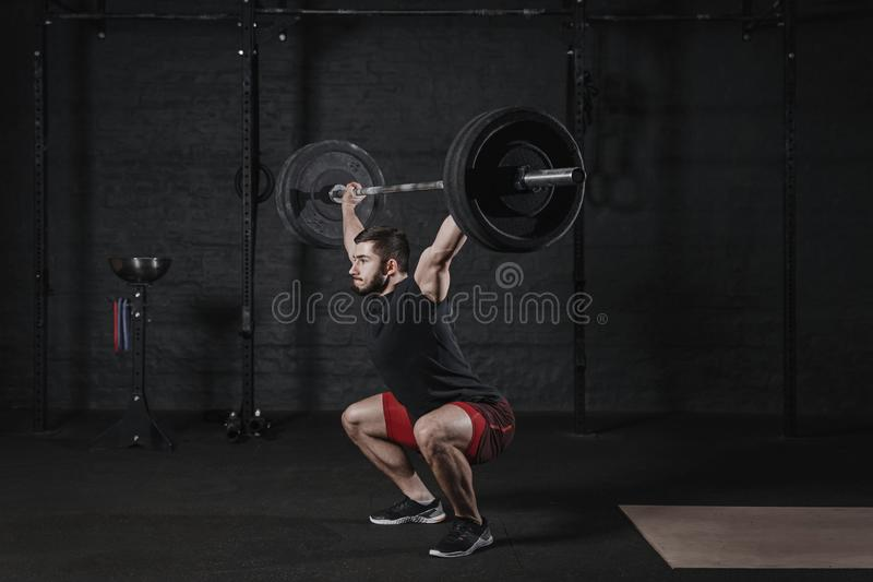 Young cross fit athlete doing squats with barbell over head. Man practicing functional training.Powerlifting workout exercises. Young cross fit athlete doing royalty free stock photography