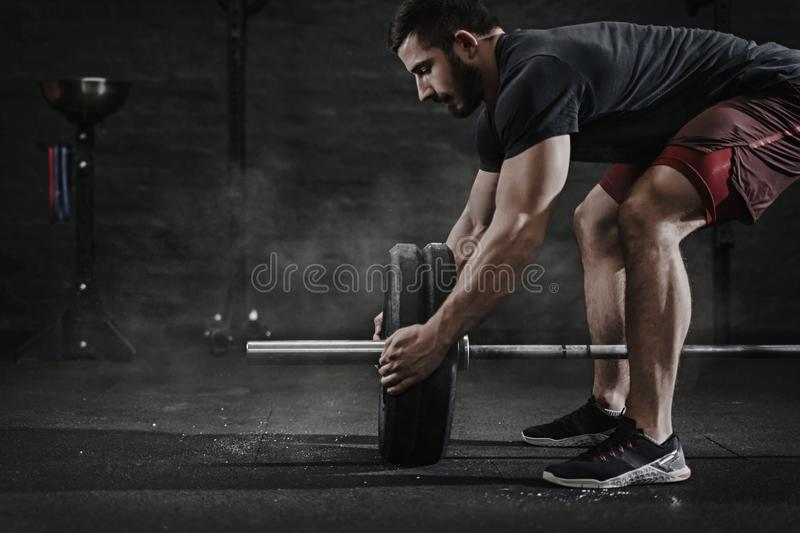 Young cross fit athlete preparing barbell for lifting weight at the gym. Barbell magnesia protection.Handsome man doing functiona royalty free stock photos