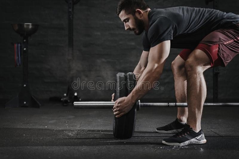 Young crossfit athlete preparing barbell lifting weight at the gym. Magnesia protection dust cloud. Handsome man doing functio royalty free stock photography