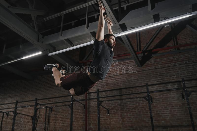 Young crossfit athlete swinging on gymnastic rings doing pull-ups at gym. Workout exercises. Young crossfit athlete swinging on gymnastic rings doing pull-ups at stock image