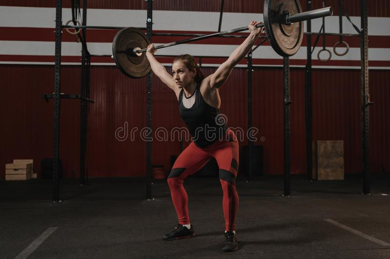 Young crossfit female athlete lifting heavy barbell overhead at the gym. Strong woman royalty free stock images