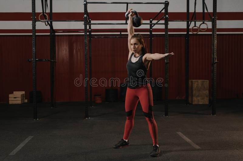 Young crossfit woman lifting a heavy weight kettlebell at gym stock photography