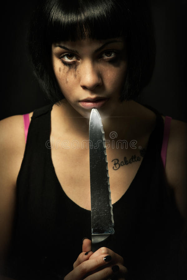 Young crying woman killer. Knife murder suicide. Crazy girl. A young girl with problems is holding a big knife and points it in her mouth. Suicide royalty free stock images
