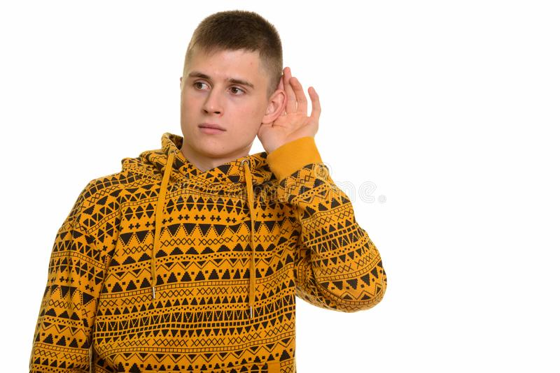 Young curious Caucasian man listening while cupping ear. Young Caucasian man listening isolated against white background stock photography