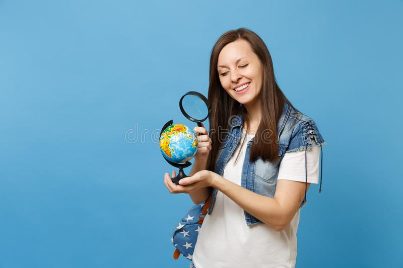 Young curious pretty woman student in denim clothes with backpack looking on world globe with magnifying glass learn. Geography isolated on blue background royalty free stock photography