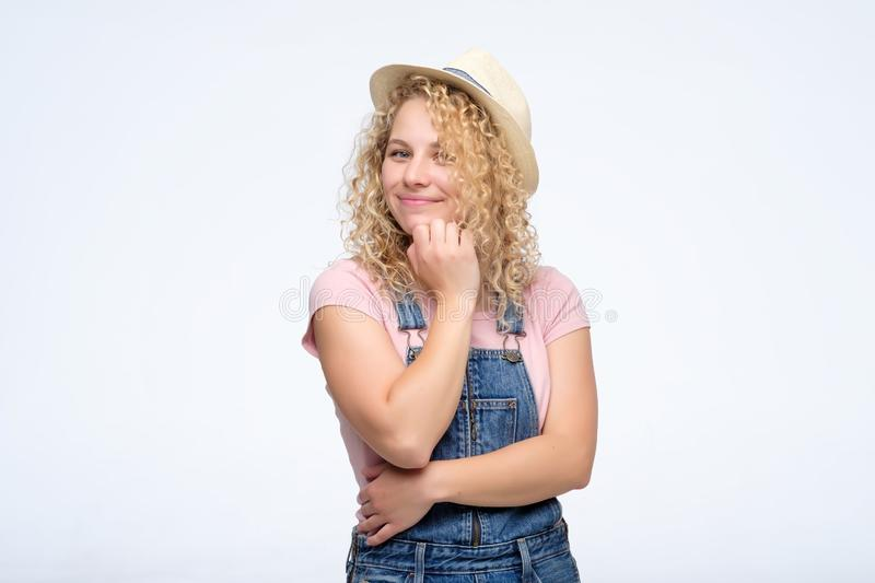 Young curly blonde woman looking confident with smile at camera stock images
