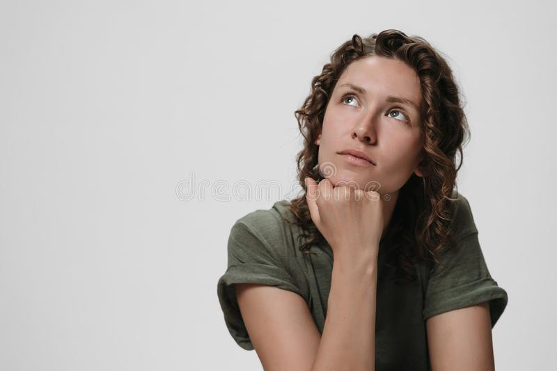 Young curly caucasian woman keeps hand under chin, being deep in thoughts. Thinks about something. Girl looks thoughtfully upwards. Copy space for your text royalty free stock photography