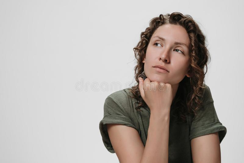 Young curly caucasian woman keeps hand under chin, being deep in thoughts. Thinks about something. Girl looks thoughtfully aside. Copy space for your text stock photo