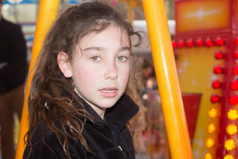 Young curly girl at the fun fair royalty free stock photography