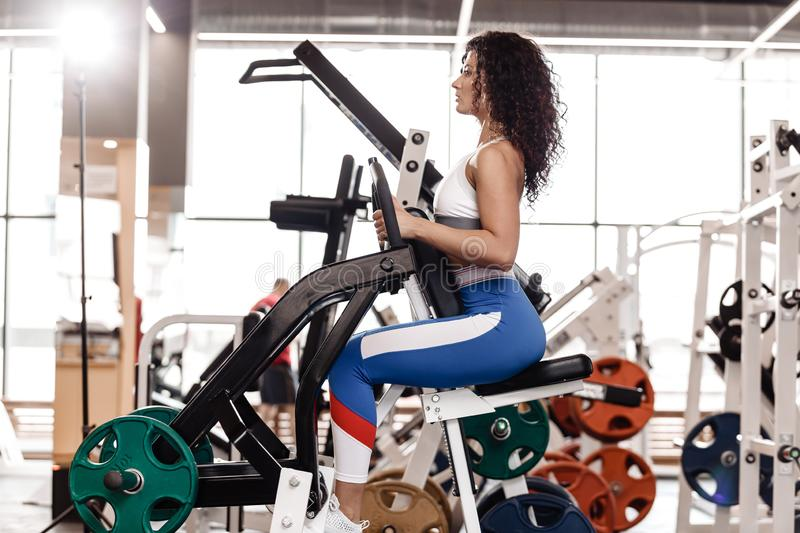 Young curly good fit girl dressed in sports clothes is doing exercise on the sports equipment in the modern gym full of. Sun light stock image