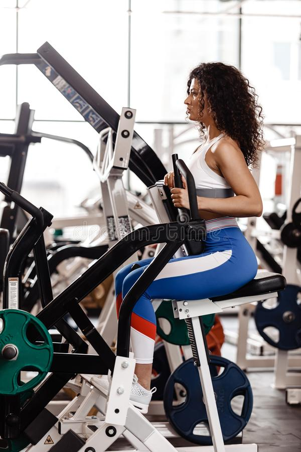 Young curly good fit girl dressed in sports clothes is doing exercise on the sports equipment in the modern gym full of. Sun light royalty free stock photo