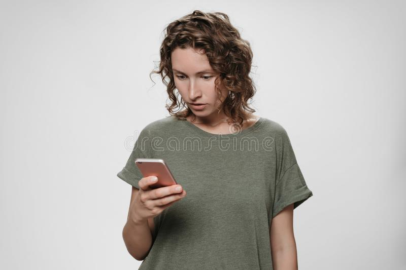 Young curly hair woman holding smartphone looks with great interest at screen. Reads important information news from web site, social networks royalty free stock images