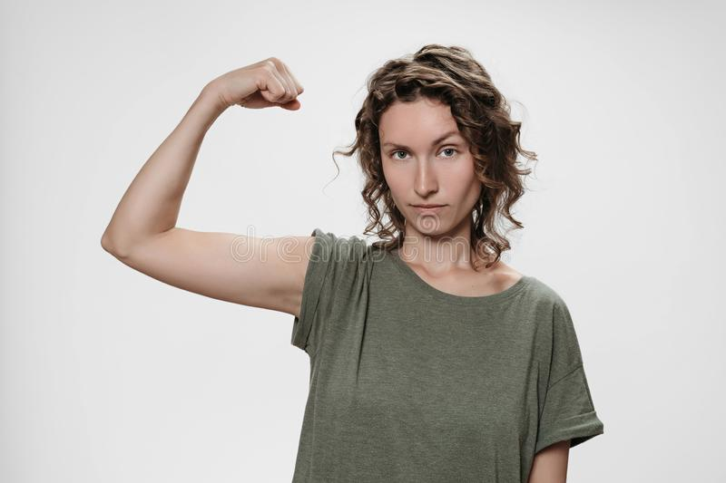 Young curly hair woman shows muscle on her hand, feels proud to be strong royalty free stock image