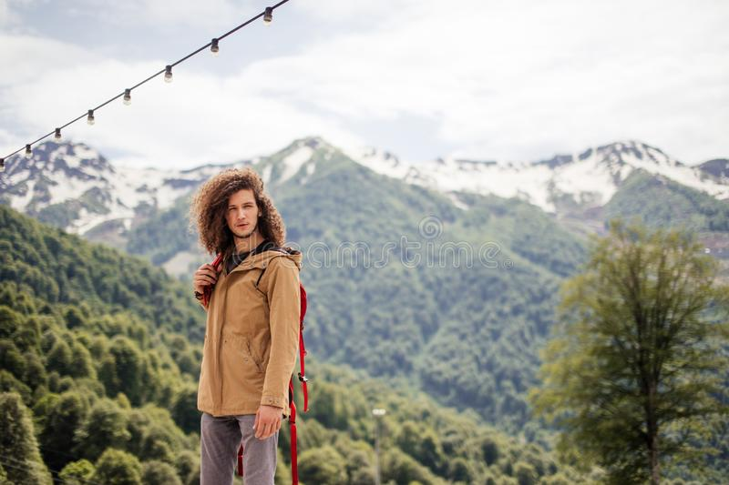 Man Traveler with red backpack relaxing outdoor with rocky mountains on background royalty free stock images